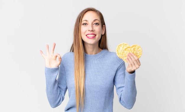 Довольно худая женщина, держащая рисовые диетические пирожные