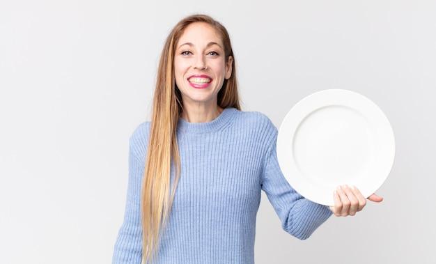Довольно худая женщина, держащая пустую чистую тарелку