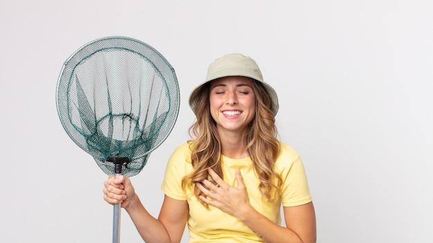 모자를 쓰고 물고기 그물을 들고 재미있는 농담에 큰 소리로 웃는 꽤 마른 여자