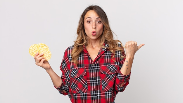 Pretty thin woman looking astonished in disbelief and holding a diet rice cakes