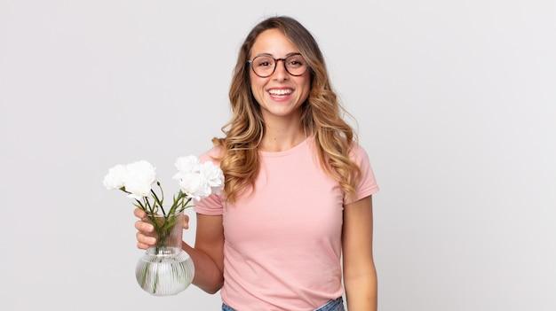 Довольно худая женщина выглядит счастливой и приятно удивленной и держит декоративные цветы