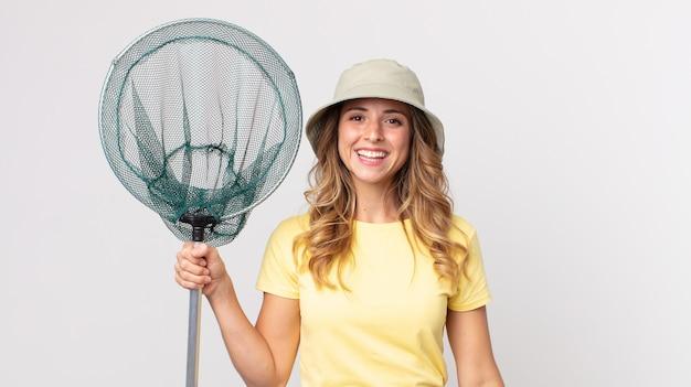 모자를 쓰고 물고기 그물을 들고 행복하고 즐겁게 놀란 꽤 마른 여자