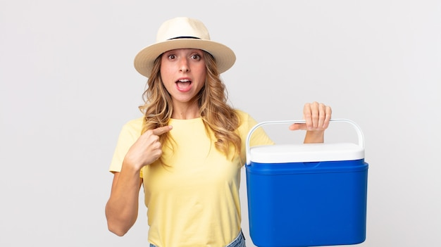 Pretty thin woman looking shocked and surprised with mouth wide open, pointing to self and holding a  summer picnic fridge