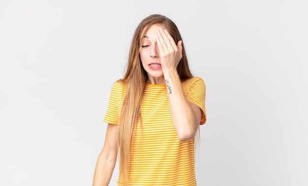 졸리고 지루하고 하품을 하고 두통과 한 손으로 얼굴의 절반을 덮고 있는 꽤 마른 여성