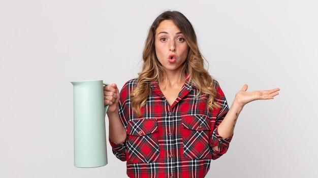 Довольно худая женщина выглядит удивленной и шокированной, с отвисшей челюстью держит предмет и держит термос с кофе