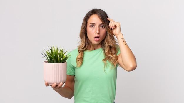 Довольно худая женщина выглядит удивленной, осознает новую мысль, идею или концепцию и держит декоративное растение