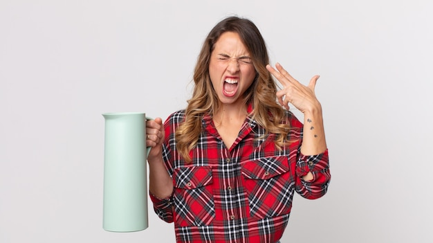 Pretty thin woman looking unhappy and stressed, suicide gesture making gun sign and holding a coffee thermos