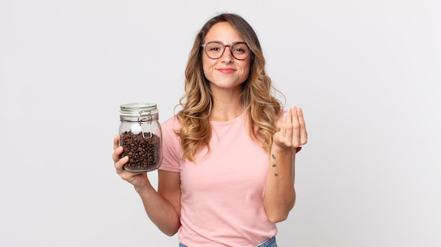 꽤 마른 여성이 돈을 지불하라고 말하고 커피 콩 병을 들고 있습니다.