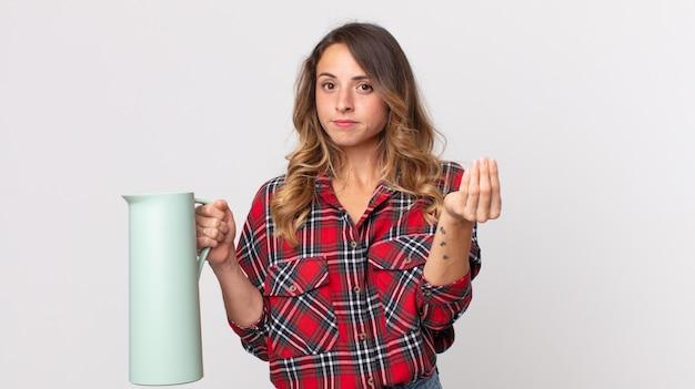 Довольно худая женщина делает каприз или денежный жест, говорит вам заплатить и держит термос с кофе