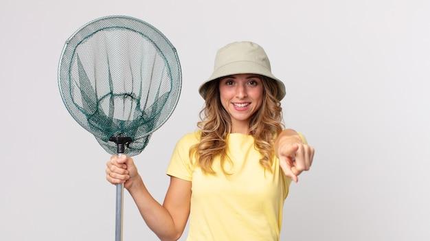 모자를 쓰고 물고기 그물을 들고 당신을 선택하는 카메라를 가리키는 꽤 마른 여자