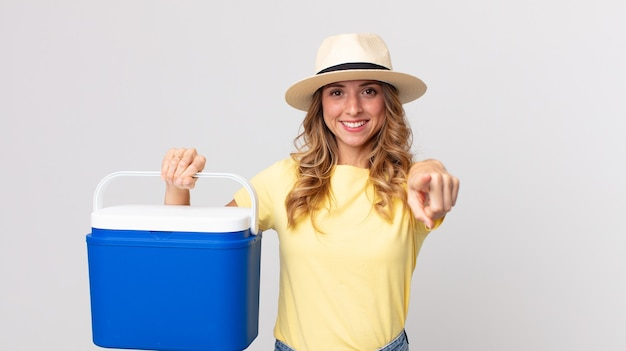 Pretty thin woman pointing at camera choosing you and holding a  summer picnic fridge