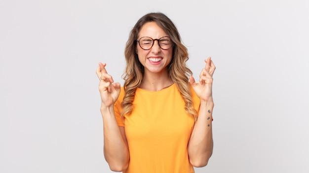 꽤 마른 여성이 웃고 걱정스럽게 두 손가락을 교차하며 걱정하고 행운을 빌거나 바라고 있습니다.