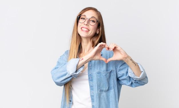 Довольно худая женщина улыбается и чувствует себя счастливой, милой, романтичной и влюбленной, делая сердечко обеими руками