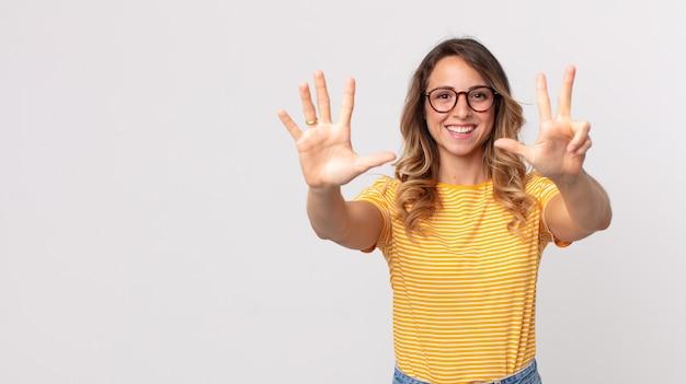 Довольно худая женщина улыбается и выглядит дружелюбно, показывает номер восемь или восьмой рукой вперед, отсчитывая