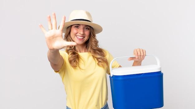 미소하고 친절해 보이는 꽤 마른 여성, 5번을 보여주고 여름 피크닉 냉장고를 들고