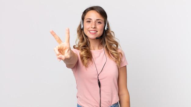 미소하고 행복해 보이는 꽤 마른 여성, 승리 또는 평화를 몸짓으로 나타내는 헤드셋을 들고 있는 운영자 조수