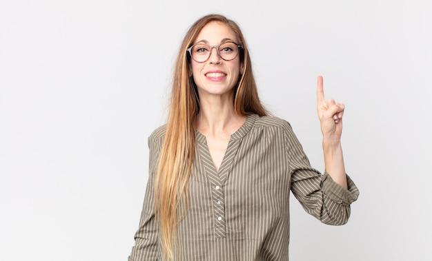한 손으로 위쪽을 가리키며 공간을 복사하여 쾌활하고 행복하게 웃고 있는 꽤 마른 여성