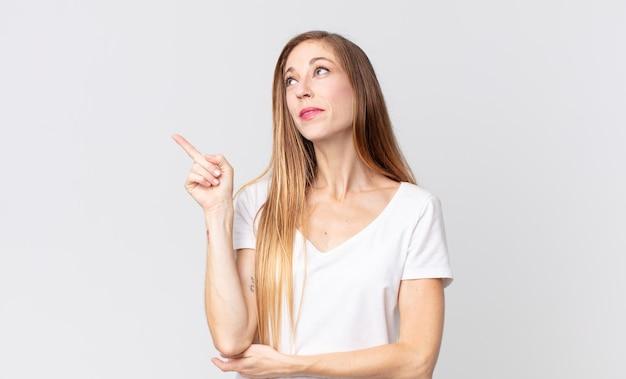 Довольно худая женщина счастливо улыбается и смотрит в сторону, задается вопросом, думает или имеет идею