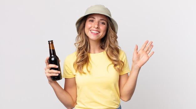 幸せそうに笑って、手を振って、あなたを歓迎して挨拶し、ビールを持っているかなり薄い女性。夏のコンセプト