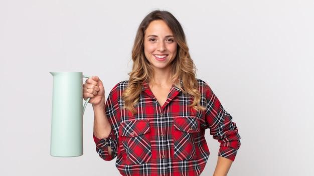 Довольно худая женщина счастливо улыбается, положив руку на бедро и уверенно и держа термос с кофе