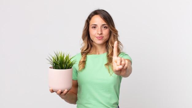 誇らしげに自信を持って笑顔でナンバーワンを作り、観賞植物を持っているかなり細い女性