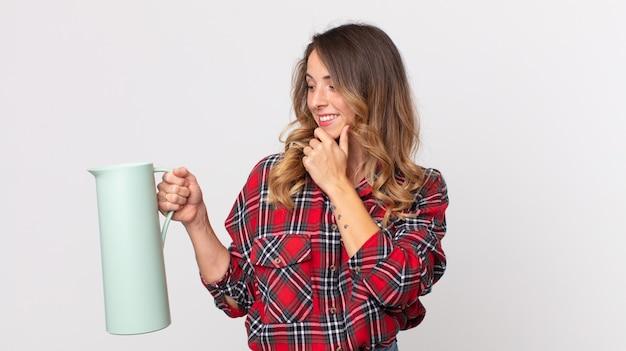 Довольно худая женщина улыбается со счастливым, уверенным выражением лица, положив руку на подбородок и держа термос с кофе