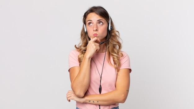 Довольно худая женщина думает, сомневается и смущается. помощник оператора с гарнитурой