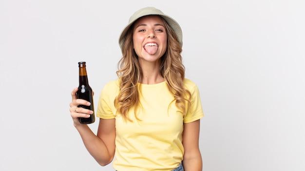 陽気で反抗的な態度で、冗談を言って舌を突き出し、ビールを持っているかなり薄い女性。夏のコンセプト