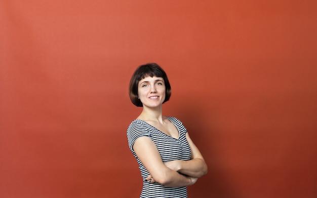 オレンジ色の背景に縞模様のドレスを着た短い髪のかなり 30 歳の女性