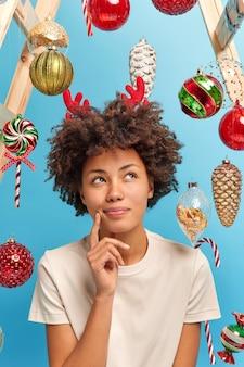 La donna afroamericana piuttosto premurosa posa pensierosa al coperto vestita con abbigliamento casual guarda sopra fa idee per una perfetta celebrazione del capodanno pensa ai regali di natale per i parenti