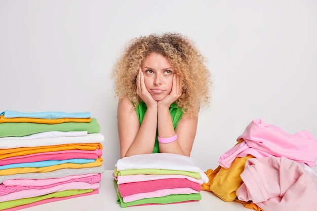 Pretty thoughtful european woman with curly hair keeps hands under chin has pensive expression folds laundry does domestic chores isolated over white