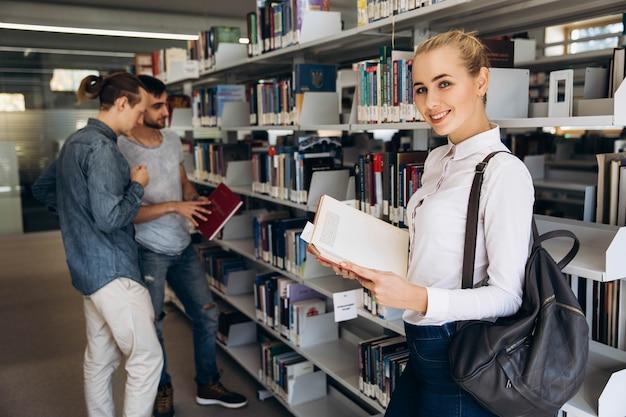 大学の図書館に立っている学生のように思慮深い少女が見える
