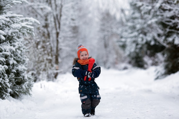 눈 덮인 날에 밖에 서 재미 겨울 옷을 입고 예쁜 유아 소녀. 소녀는 눈덩이를 만들고있다. 공간 복사