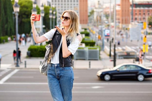 Donna bionda abbastanza turistica che fa selfie sulla strada