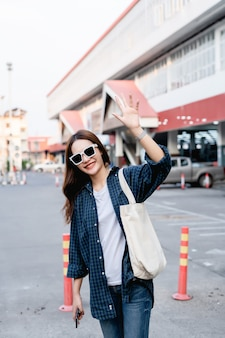 Bella ragazza turistica in occhiali da sole che porta una grande borsa sulla spalla in piedi e alza la mano per salutare e sorridere