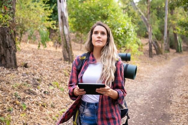 地図付きのタブレットを持って目をそらしているかなりの観光客。自然の上をハイキングまたはウォーキングし、バックパックを運ぶ白人の長い髪の女性。観光、冒険、夏休みのコンセプトをバックパッキング
