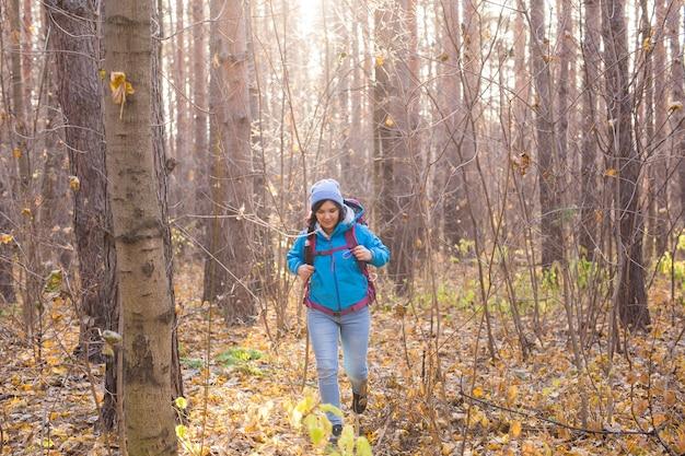 가을 자연 배경 위에 배낭을 메고 걷는 예쁜 관광 여성