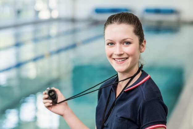 Pretty trainer holding stopwatch at the pool