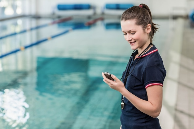 Pretty trainer looking at stopwatch at the pool
