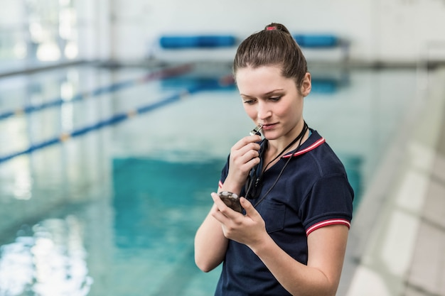 Pretty trainer looking at stopwatch with whistle at the pool