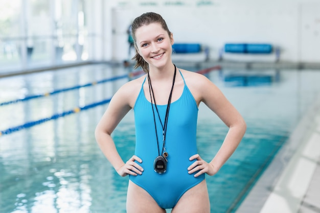 Pretty trainer standing with hands on hips at the pool