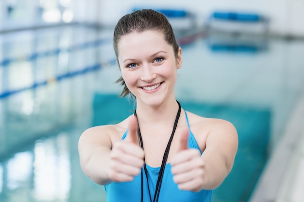 Pretty trainer with thumbs up at the pool