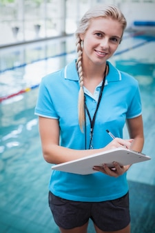 Pretty trainer writing on clipboard at the pool
