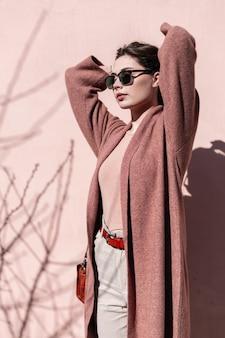 도시에서 빈티지 핑크 벽 근처 태양에 서있는 포즈 유행 선글라스에 섹시 한 입술으로 꽤 유행 아름 다운 젊은 여자. 세련된 착용에 우아한 소녀는 고급스러운 머리카락을 곧게 만듭니다. 레트로 스타일