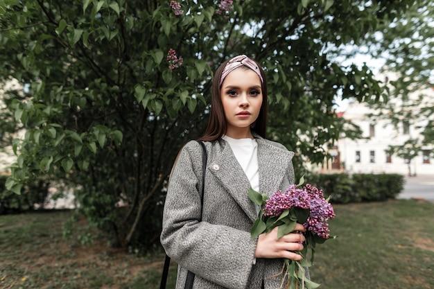 캐주얼 코트에 빈티지 반다나를 입은 꽤 트렌디한 젊은 여성이 화창한 봄날 거리에 꽃다발 라일락과 함께 서 있습니다. 보라색 꽃과 함께 매력적인 매력적인 소녀는 야외에서 산책. 자연의 아름다움.