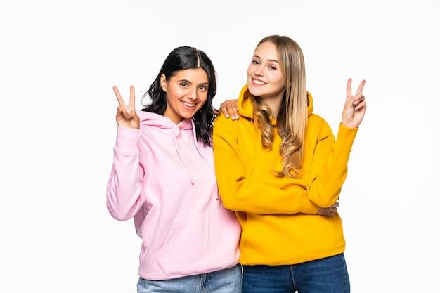 Due ragazze carine che mostrano i simboli del v-sign, indossano felpe con cappuccio luminose casuali e jeans isolati muro bianco