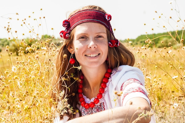 Pretty ukrainian woman dressed in embroidered clothes in the field