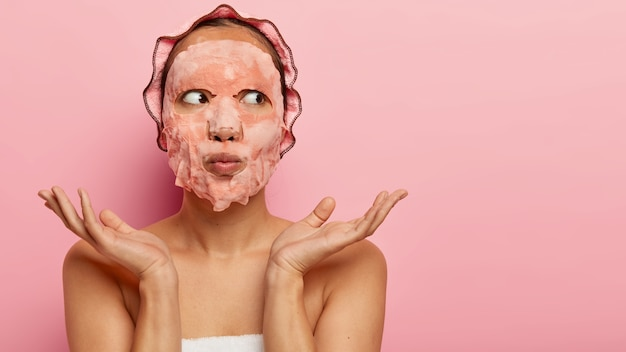 Pretty unaware woman with sheet soap facial mask, cares about beauty, wants to have healthy skin, spreads palms sideways over shoulders