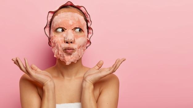 시트 비누 페이셜 마스크를 쓴 꽤 알지 못하는 여성, 아름다움에 대한 관심, 건강한 피부를 갖고 싶어, 손바닥을 어깨 너머로 옆으로 펼칩니다.