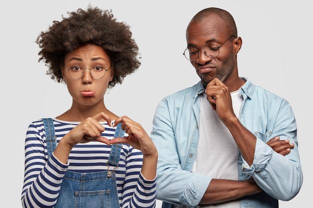 Giovane femmina tenebrosa abbastanza infelice con l'acconciatura afro